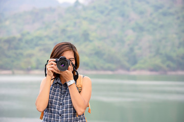 Hand woman holding the camera Taking pictures background Wang Bon dam Nakhon nayok , Thailand