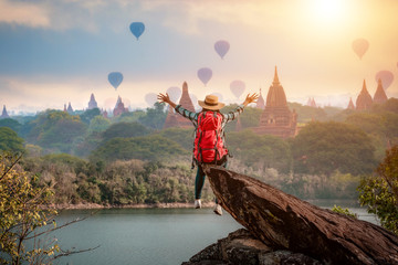 Woman traveler sitting on stone freedom hands up watching and enjoying with Bagan pagoda landscape  in Mandalay Myanmar. Fototapete