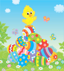 Little yellow Easter Chick on a pile of colorfully decorated eggs on green grass on a sunny spring day, vector illustration in a cartoon style