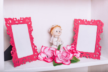 The angel folded his hands in prayer. Porcelain toy surrounded by flowers on a wooden shelf. Two pink photo frames