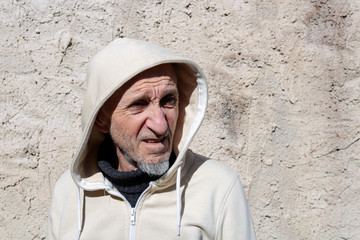 Portrait of senior man in hood in front of a wall