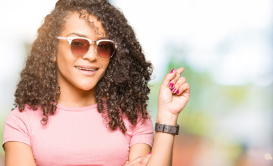 Young beautiful woman with curly hair wearing pink sunglasses with a big smile on face, pointing with hand and finger to the side looking at the camera.