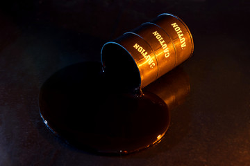 Opened toy barrel of oil on dark background