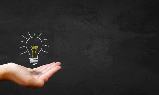 Chalkboard & Hand Showing Light Bulb