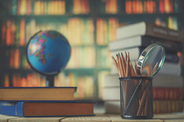 Textbooks,  globe and pencils on a wooden background. Educational background Fototapete