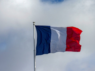 Deep and reach colors fabric tricolour flag of France fluttering in the wind