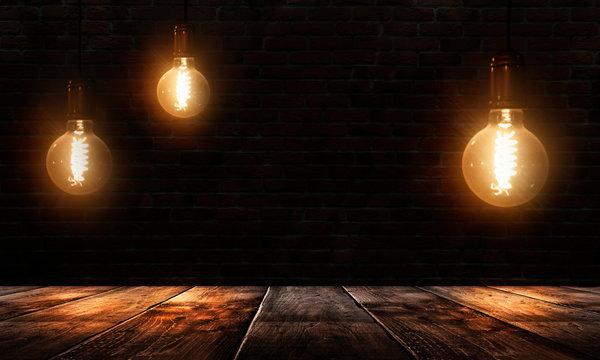 Dark empty room, wooden table, brick walls, lamps. Night view.