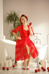 beautiful pin up girl with red hair posing in a sexy lace robe in her bathroom