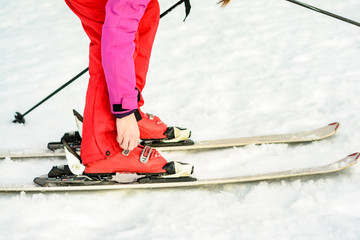 Woman in red-pink clothes wearing ski footwear for skiing