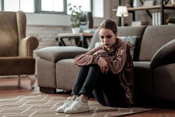 Teenage girl wearing white sneakers sitting on the floor feeling stressed