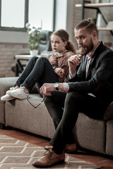 Father and daughter sitting on sofa after big nervous quarrel