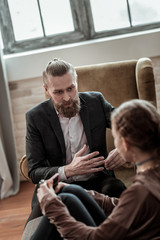 Bearded psychologist giving instructions to stressed teenager