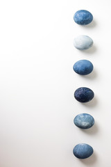 Six colored blue, gray marbled eggs, similar to stones, lie in a row on a white background