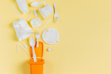 White single use plastic in garbage bin on  yellow background..Concept of Recycling plastic. Flat lay, top view