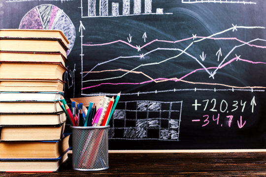 Books on the table against the background of a chalkboard on which are drawn graphs and charts of growth and decline. Business training school.