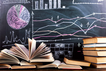 Books on the table against the background of a chalkboard on which are drawn graphs and charts of...