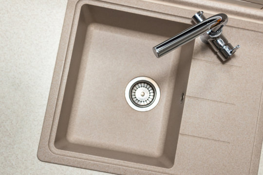 Granite kitchen sink with stainless two-handle faucet. Top view with copy space