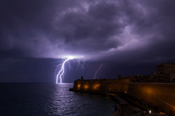 A lightning bolt strikes the sea near Fort St Elmo during a storm in Valletta