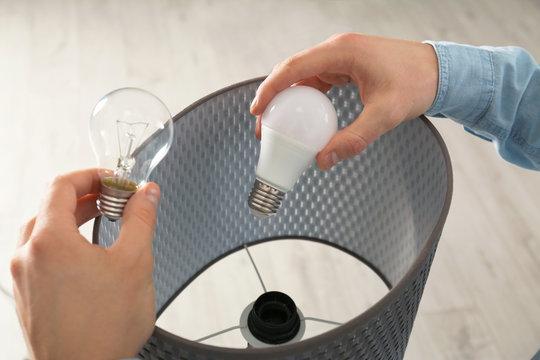 Man changing light bulb in lamp indoors, closeup