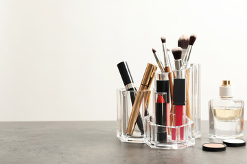 Lipstick holder with different makeup products on table against white background. Space for text
