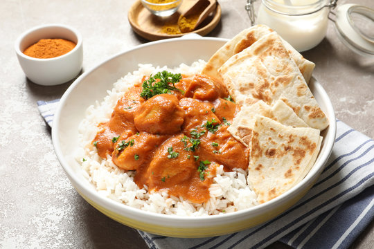 Delicious butter chicken with rice in plate on table