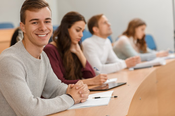 Handsome male student sitting at table in lecture hall, looking at camera and smiling. Cheerful man writing notes and enjoying studying process at university. Concept of interesting education.