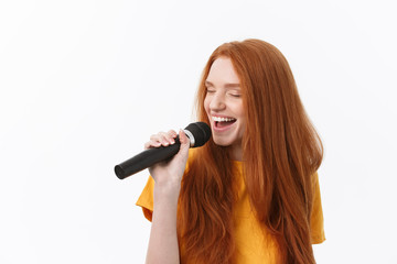 Image of happy woman with curly hair singing while holding microphone isolated over white background Fotobehang