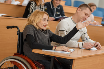 Happy female student in wheelchair sitting at table and raising hand at university. Smiling woman answering and talking during lesson in lecture hall. Concept of available education