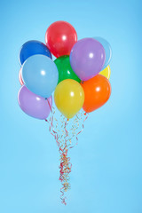 Bunch of bright balloons on color background