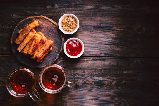 lager beer and snacks. bar table. restaurant, pub, food concept. delicious drink and breaded cheese sticks with sauces set. friday party atmosphere, craft brewery background
