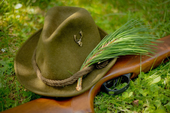 Hunter's green hat with emblem of the deer with a weapon lying on the grass in the forest