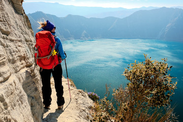 Young tourist girl enjoying spectacular view of green Quilotoa volcaninic lake in Ecuador South America Wall mural