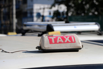 Broken taxi light sign or cab sign in drab white and red color with white text on the car roof at the street.