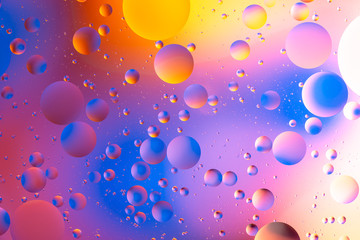 purple and orange oily drops  in water with colorful background, close-up