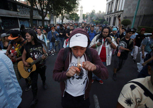 A participant smokes a pipe with marijuana during a march in support of the legalization of marijuana in Mexico City