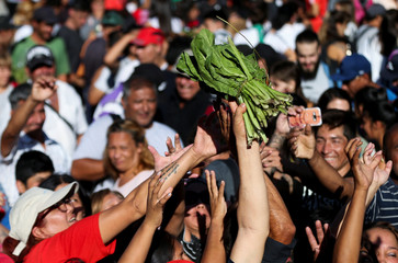 People receive spinach from a farmer during a protest outside the Casa Rosada Presidential Palace in Buenos Aires