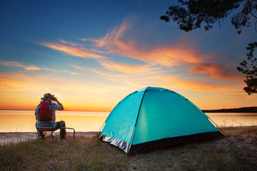 Wall Mural - Family resting with tent in nature at sunset