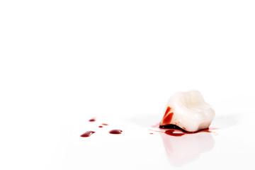 Konzeptbild mit blutigem Zahn vor weißem Hintergrund