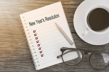 New Year's Resolution words and check list marks in notebook with glasses, pencil and coffee cup on wooden table. Business concept.