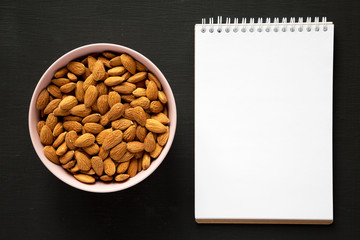 Full pink bowl of almonds, blank notepad on black background, overhead view. Flat lay, from above, top view. Space for text.