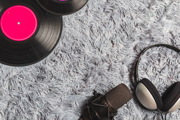 headphone, microphone and vinyl record on grey carpet. music background