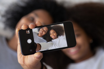 African mother daughter photographing showing selfie photo on smartphone