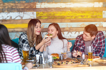 Group of young friends sharing slice of pizza while smiling and enjoying time together