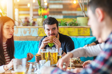 Young man enjoying burger and friends company at restaurant