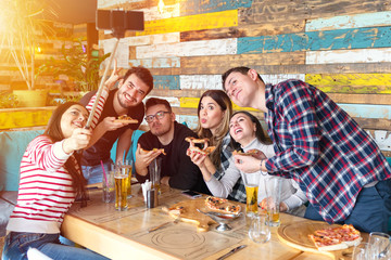 Cheerful young friends taking selfie with smart phone while sharing a pizza