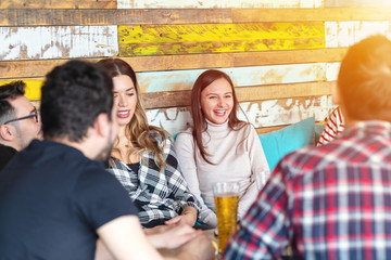 Group of young friends having great time together drinking beer in bar.