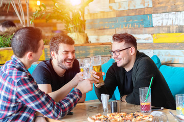 Group of three young men enjoying drink at rusitc bar