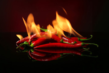 Canvas Prints Hot chili peppers Red hot chili peppers with fire on dark color background