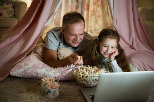Family quality time. Father and daughter lie in homemade pink tent with flowers, watch cartoons on laptop, eating popcorn, laugh. Cozy stylish room. Family bonds concept