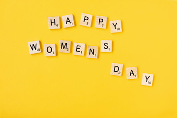 Top view Message happy woomans day spelled in wooden blocks on yellow background. Love, 8 march background. Gift, greeting, compliment concept. Copy space. place for text
